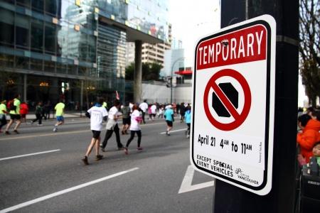 no correr: VANCOUVER, Canad� - 21 de abril 2013-A no parar signo revelador de tr�fico no pueden parar aqu� espec�ficamente en 21 de abril de 2013 por el Vancouver Sun Run. Los participantes de la Sun Run se pueden ver en el fondo pasando por el hip�d Editorial