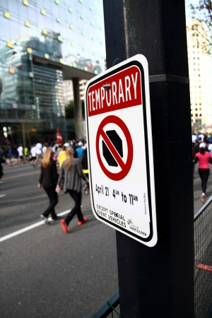 VANCOUVER, CANADA - April 21, 2013 - A no stopping sign telling traffic they can not stop here specifically on the 21st of April, 2013, because of the Vancouver Sun Run.  Participants of the Sun Run can be seen in the background passing by on the race cou