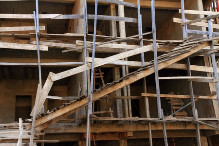 poorly: A very dangerous construction site with poorly constructed wooden scaffolding
