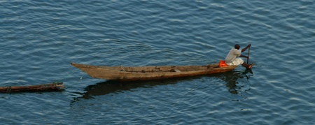 long lake: A lone African man paddles his long boat across a lake while pulling some logs