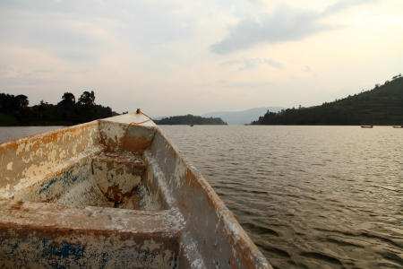bunyoni: A boat with faded and peeling paint reaches out into the waters of Lake Bunyoni in Uganada