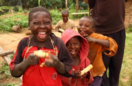 bunyoni: LAKE BUNYONI, UGANDA - CIRCA SEPTEMBER 2012.  A group of Ugandan children smile while enjoying eating sugarcane near Lake Bunyoni, Uganda during September 2012.