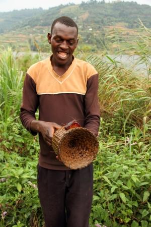bunyoni: LAKE BUNYONI, UGANDA - CIRCA SEPTEMBER 2012. A Ugandan man displays a crayfish on a wicker crayfishing trap on the shores of Lake Bunyoni during September 2012.