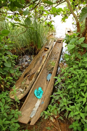 bunyoni: Two dugout canoes sit along the shoreline on Lake Bunyoni in Uganda   Nearby a crayfish trapper has placed his traps