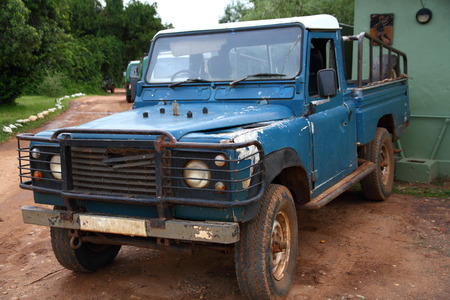 old blue safari truck covered in dirt, rust and with chipping paint photo