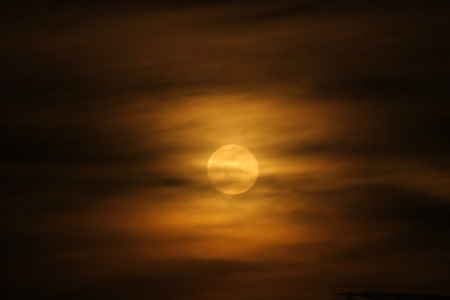 A full moon rises throgh the orange clouds of evening in Uganda, Africa