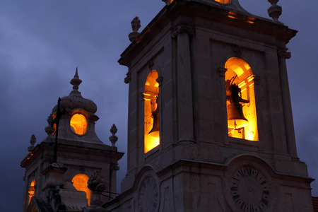A spooky and dark church bell tower with the bells lit up by lights on the inside  Stock Photo