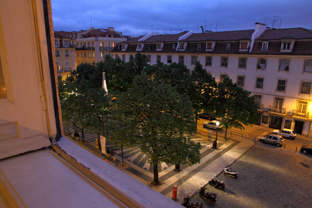 Looking out an apartment window in Lisbon to the tiled and treed plaza square below at night