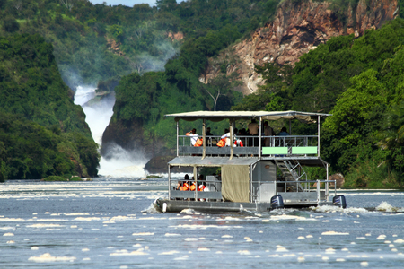 A double level river cruise boat takes passengers up the Nile River to Murchison Falls in Murchison Falls National Park, Uganda.