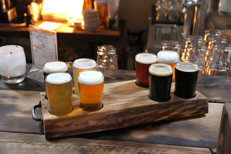 Eight beer samples in a burned wood holder on a burned wood table in a warm room. Imagens