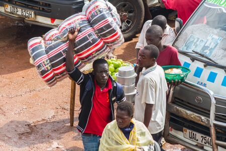 KAMPALA, UGANDA - OCTOBER 03, 2012.  A man carries a mattress above his head at the taxi park in Kampala, Uganda on October 03,2012.