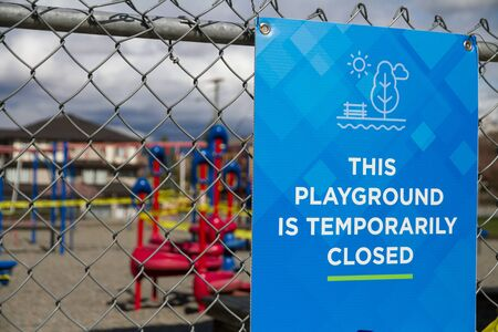 This Playground Is Temporarily Closed Sign with playground taped off in background