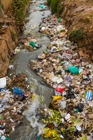 A heavily polluted river filled with all kinds of garbage, trash, and sewage in the Kibera slum of Nairobi, Kenya.