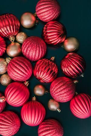 赤と金のクリスマスボールの装飾品は、彼らがクリスマスツリーに置かれるのを待っているテーブルの上に座っているように上から撮影されていま