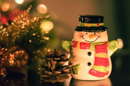 A tiny ceramic snowman suited up with a scarf and black top hat is standing with a smile on his face and arms open around other christmas decorations.