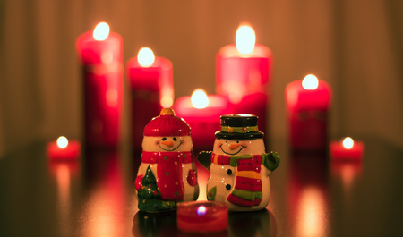 Male and female ceramic snowman with red burning candles around them. Stock Photo