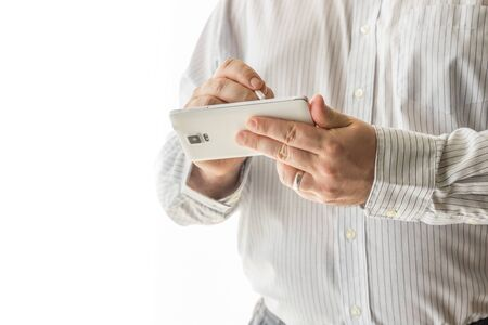 A business man is is holding on to his white cellphone. The man is using his stylus pen for work on his cell phone. The background is all white. The businessman is wearing a button down white striped shirt. Stock Photo