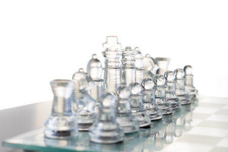 A clear glass chess set is set up and ready to play. The background is all white. Archivio Fotografico