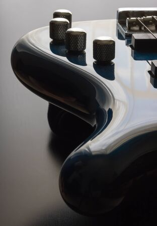 A blue five string bass guitar is strategically positioned in the frame with a black wooden background. This is a darker image which emphasizes the sleek shape of the guitar along with a play on light and shadows.