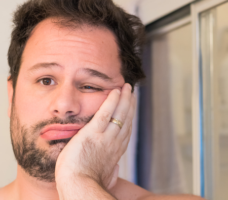 A young adult Caucasian male has his hand on his cheek as he hesitates to get ready for work.