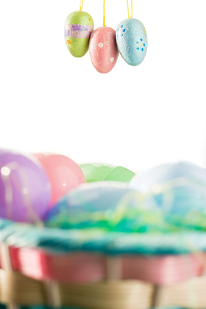 This Easter Basket is filled with easter eggs and is set in front of a white background. Three decorated baby Easter Eggs are dangling above the basket.