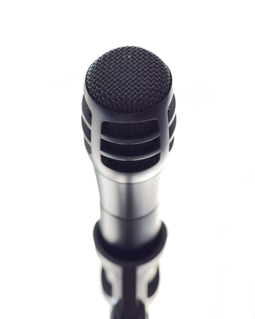 A sleek black microphone on a stand in front of open white space.