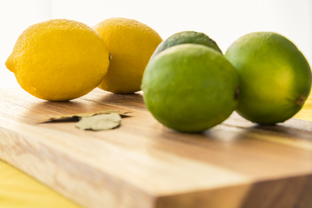 A whole lemon is isolated among other fresh fruit. The fruit are all set on a wooden cutting board and yellow table top with a white background. Imagens