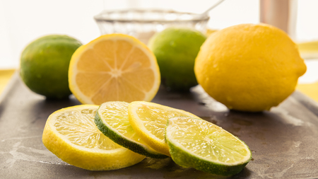 Fresh lemon and lime slices are set in front of whole and sliced fruit with a small bowl of sugar for making fresh lemonade.