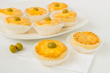 Small brazilian chicken pie pastries (Empadinhas) are  set on a white table top surface complete with a napkin, silverware, and serving plate, serving plate, and decorative green olives.