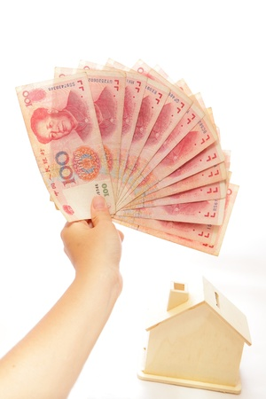 Money on hand with a house piggy bank photo
