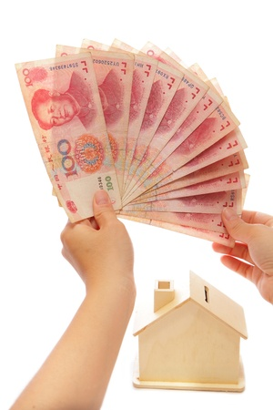 disillusioned: Money on hand with a house piggy bank
