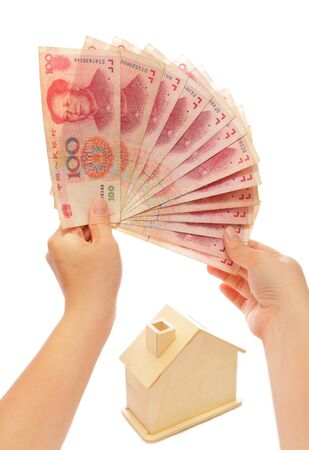 Money on hand with a house behind photo