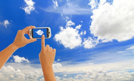 mobility: Hand holding smart phone with blue sky on white