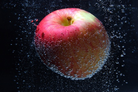 Apple in the water with crystal bubbles photo