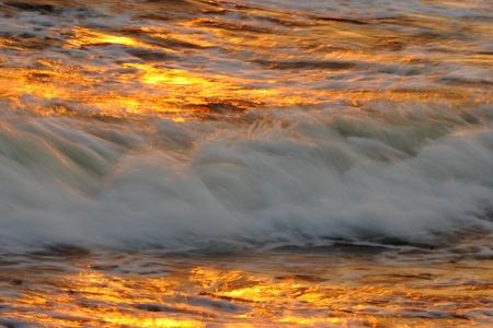 黄金の夕日と海の波