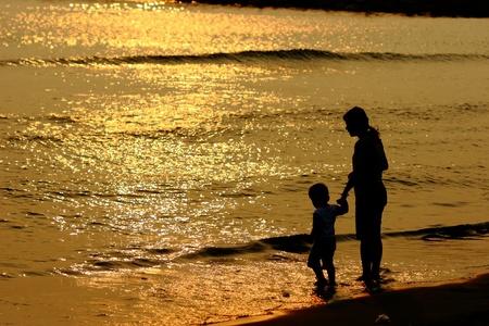 Mother and a child in golden sunshine with beautiful sea   photo