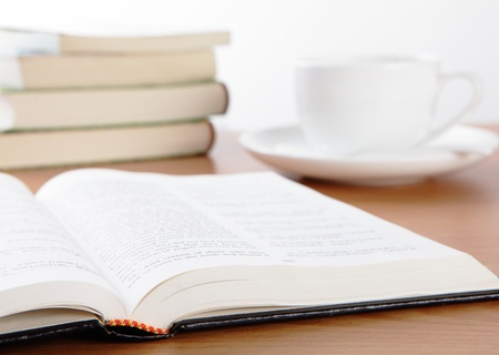 Cup book and plant on wooden table  photo