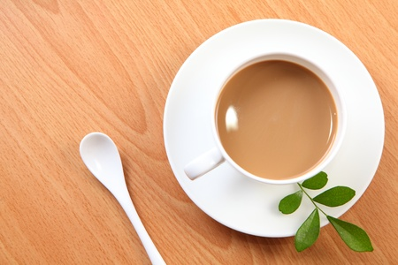 latte coffee in a white cup with green leaf and wood texture background  photo