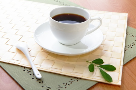 styled interior: Black coffee in a white cup with green leaf and wood  Stock Photo