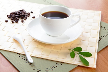 Black coffee in a white cup with green leaf and wood  photo