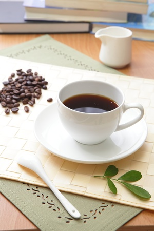 Black coffee in a white cup with green leaf and wood texture background photo