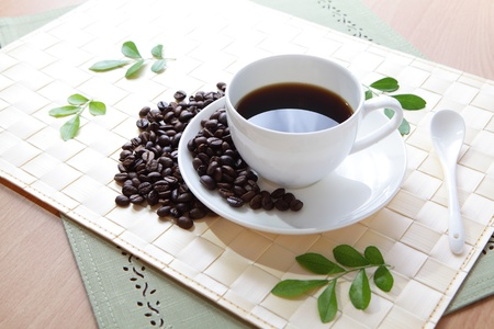 Coffee bean and hot coffee with green leaf  photo