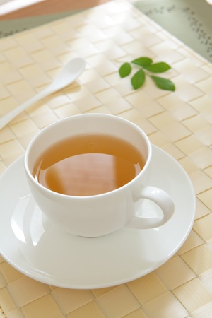 teatime: a cup of green tea with morning sunlight from window and green leaf  Stock Photo