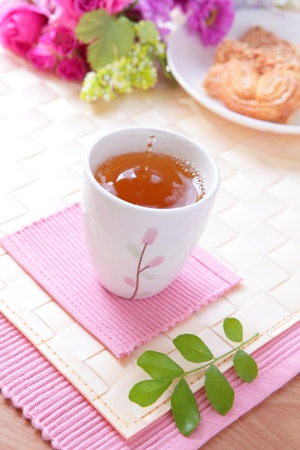 warmly: cup of black tea with cookie and beautiful flowers and water drop