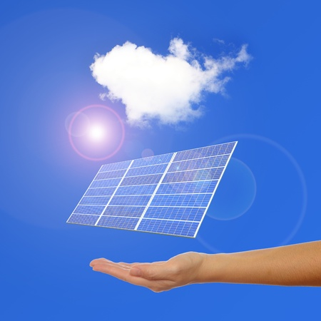 hand with Solar Panel , sunlight and blue sky background photo