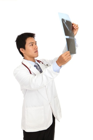 x ray equipment: Young asia doctor checking x-ray carefully
