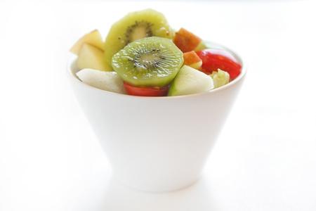 glass bowl: fresh fruit salad with kiwi,tomato,apple,etc.