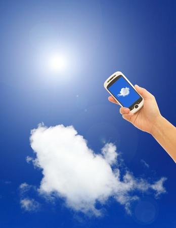 Mano azienda di telefonia mobile con sfondo blu cielo, concetto di cloud computing