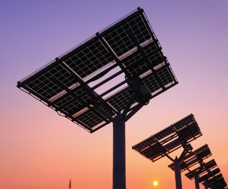 cobradores: silueta del panel solar con hermosa puesta de sol Foto de archivo