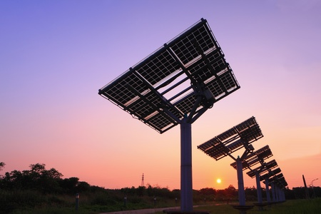 solar power plant: silhouette of solar panel with beautiful sunset